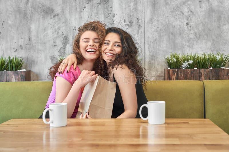 Meninas felizes aperto, guardando o presente do saco de papel no café fotografia de stock royalty free