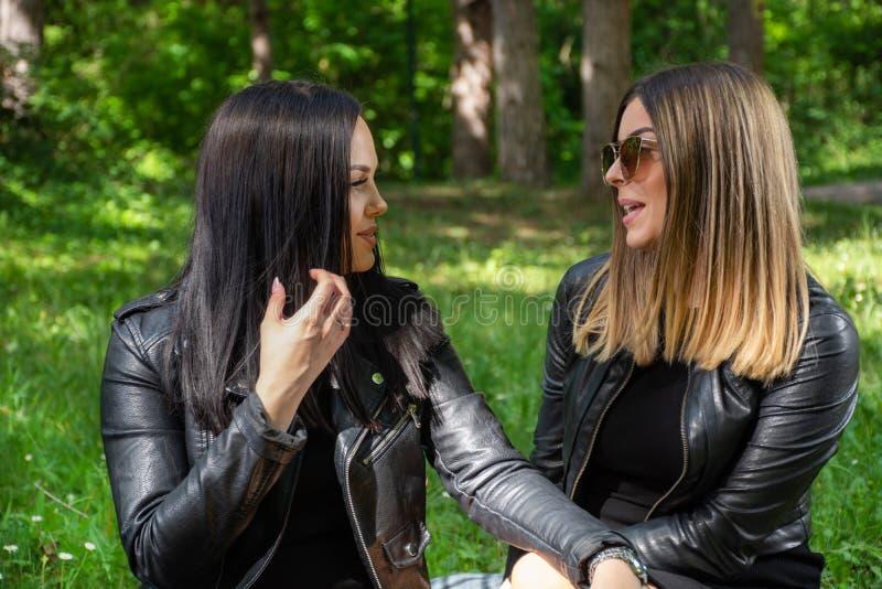 Meninas felizes bonitas que falam na natureza e que sentam-se no prado em uma cobertura, em um riso da mulher e para apreciar em  imagem de stock royalty free