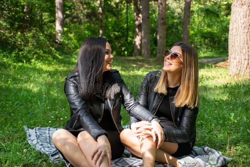 Meninas felizes bonitos que falam na natureza e que sentam-se no prado em uma cobertura, em um riso da mulher e para apreciar em  foto de stock royalty free