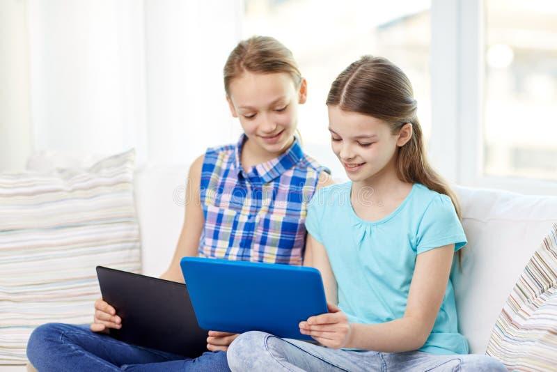 Meninas felizes com o PC da tabuleta que senta-se no sofá em casa fotografia de stock