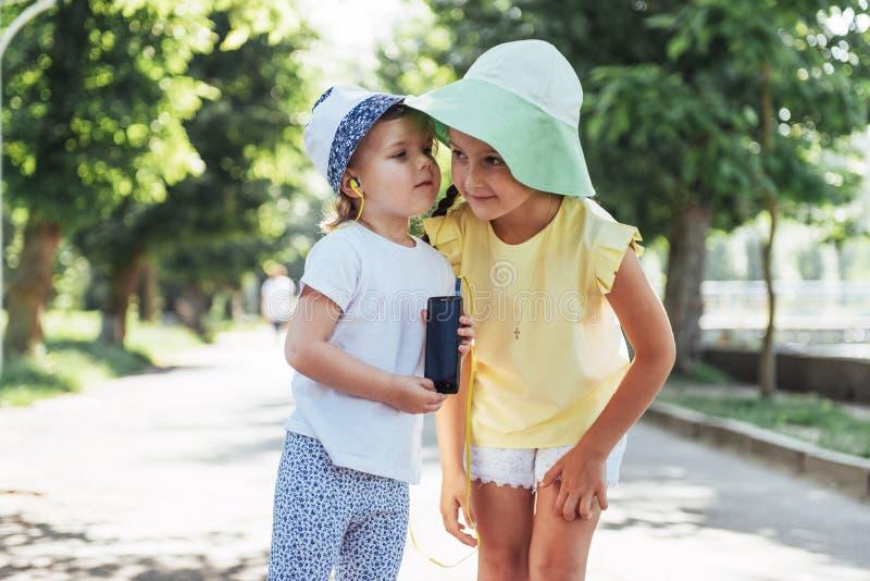 Meninas felizes com os fones de ouvido para compartilhar da música fotografia de stock