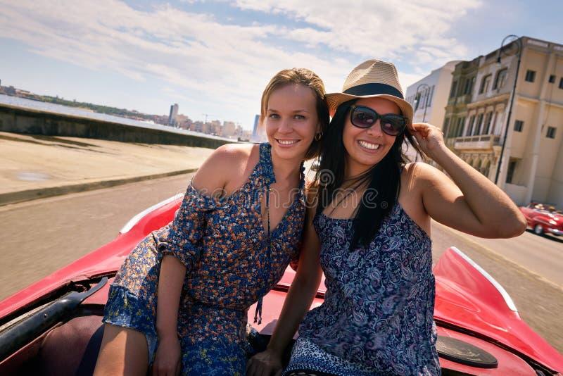 Meninas felizes do turista dos pares no carro Havana Cuba do vintage fotografia de stock