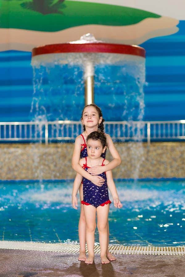 Meninas felizes em fatos de banho idênticos, posando perto da piscina infantil no parque aquático Criança aprende a nadar fotografia de stock