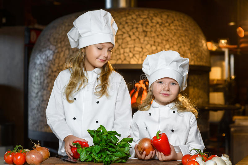 Meninas felizes engraçadas do cozinheiro chefe que cozinham no restaurante foto de stock