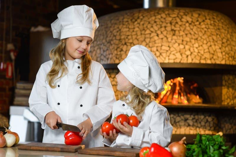 Meninas felizes engraçadas do cozinheiro chefe que cozinham no restaurante imagem de stock royalty free