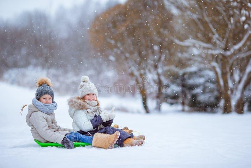 Meninas felizes pequenas adoráveis que sledding no dia nevado do inverno fotografia de stock