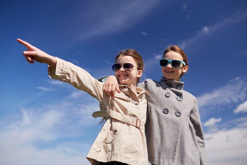 Meninas felizes que abraçam e que apontam o dedo fotos de stock royalty free