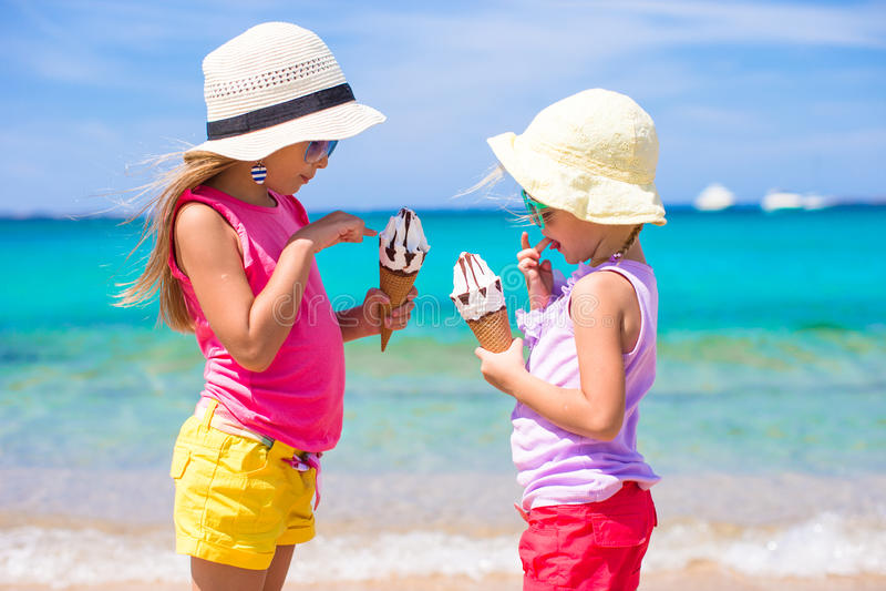 Meninas felizes que comem o gelado sobre o fundo da praia do verão Povos, crianças, amigos e conceito da amizade fotos de stock