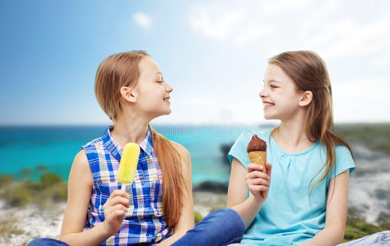 Meninas felizes que comem o gelado sobre a praia imagem de stock royalty free