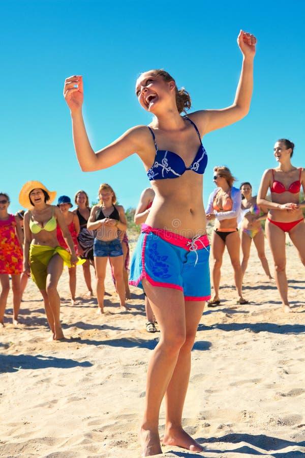 Meninas felizes que dançam na praia imagem de stock