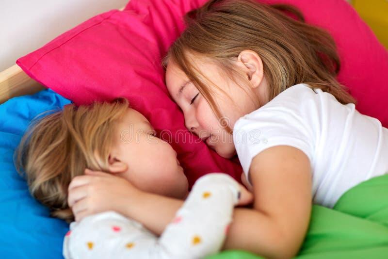 Meninas felizes que dormem na cama em casa imagem de stock
