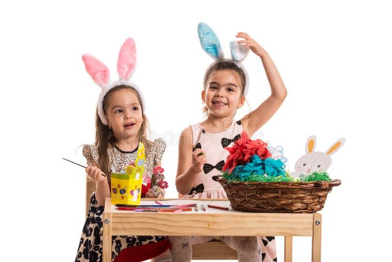 Meninas felizes que fazem decorações da Páscoa fotografia de stock royalty free