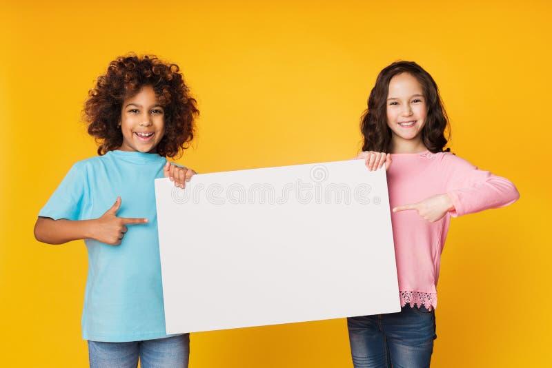 Meninas felizes que mostram a placa vazia e que apontam nela fotografia de stock royalty free