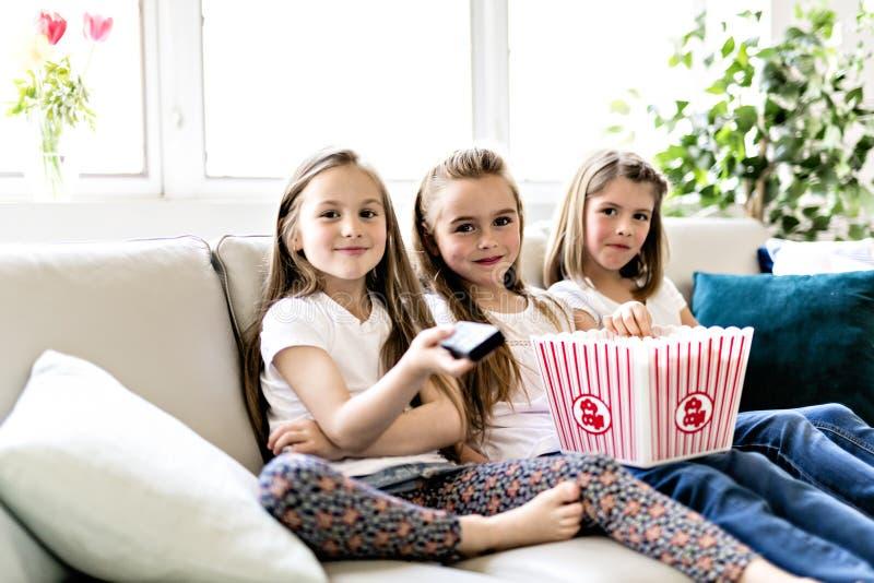 Meninas felizes que olham o filme da comédia na tevê e que comem a pipoca em casa imagem de stock