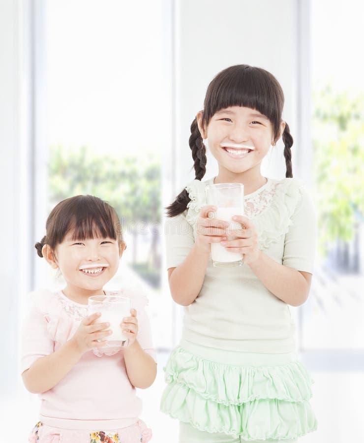 Meninas felizes que prendem o leite fresco fotos de stock