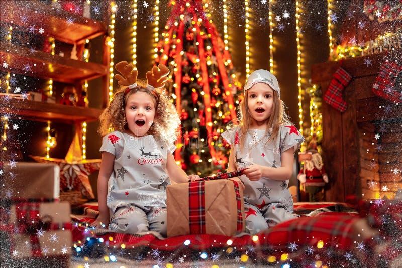 Meninas felizes que vestem a caixa de presente aberta dos pijamas do Natal por uma chaminé em uma sala de visitas escura acolhedo fotografia de stock royalty free