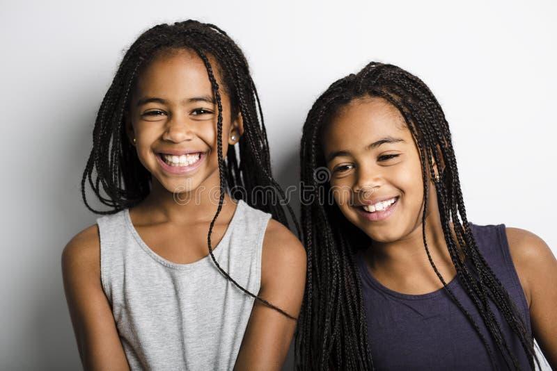 Meninas gêmeas africanas adoráveis no fundo do cinza do estúdio fotografia de stock royalty free