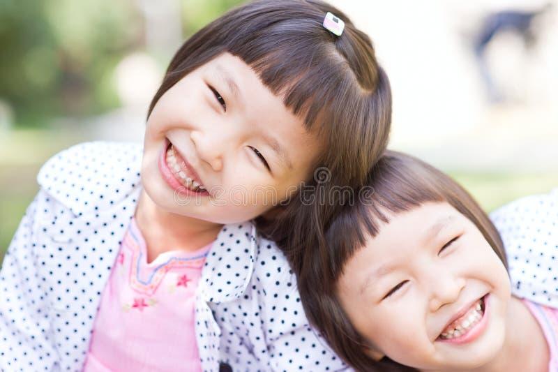 Meninas gêmeas asiáticas de sorriso fotografia de stock