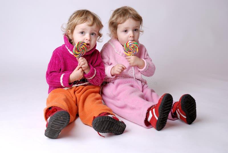 Meninas gêmeas com lollipops fotografia de stock