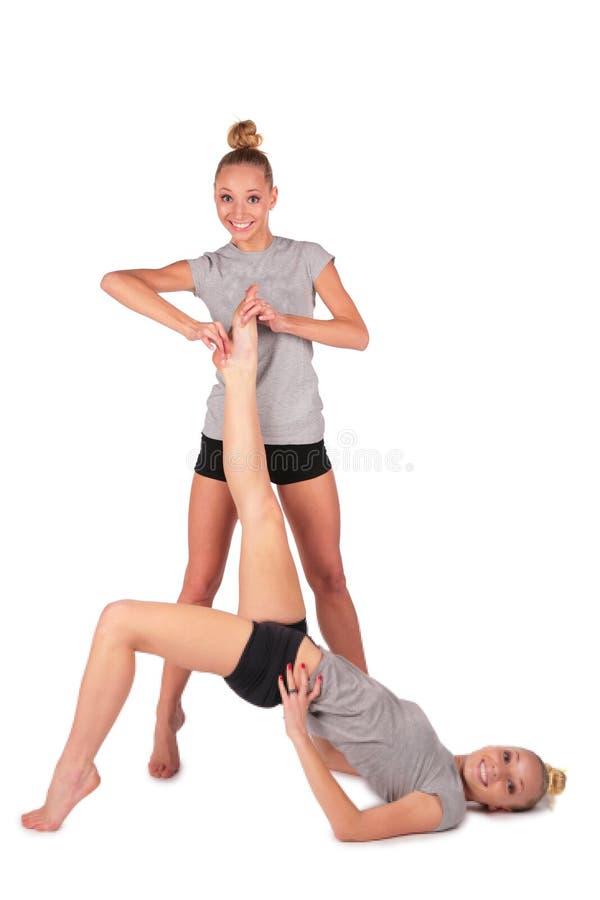 Meninas gêmeas do esporte. prendendo o pé da irmã de encontro imagens de stock royalty free