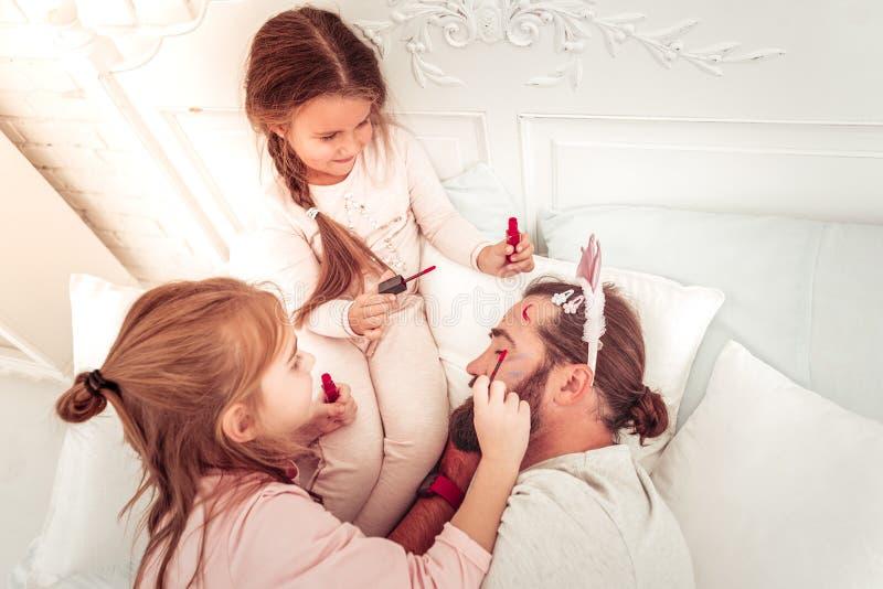 Meninas impertinentes deleitadas que pintam sua cara dos pais fotos de stock