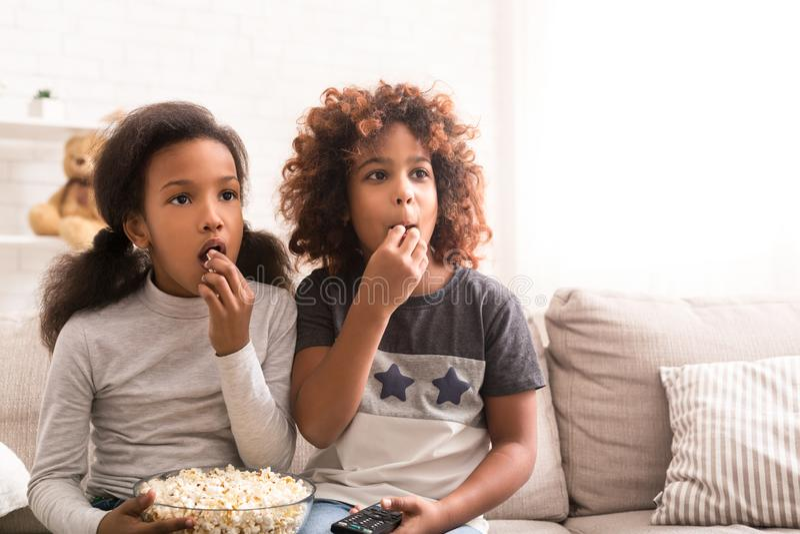 Meninas interessadas que olham o filme da descoberta e que comem a pipoca imagem de stock royalty free