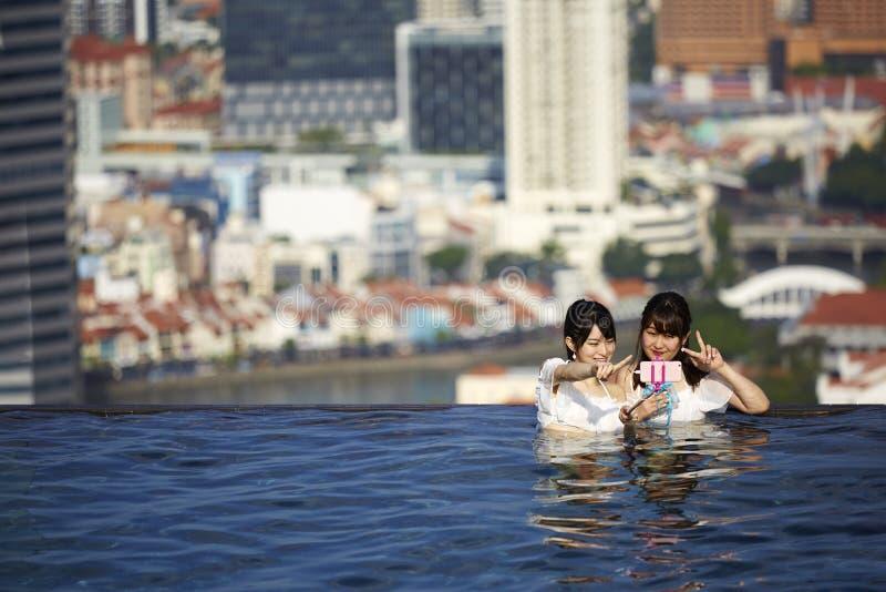 Meninas japonesas que tomam selfies na piscina fotos de stock royalty free