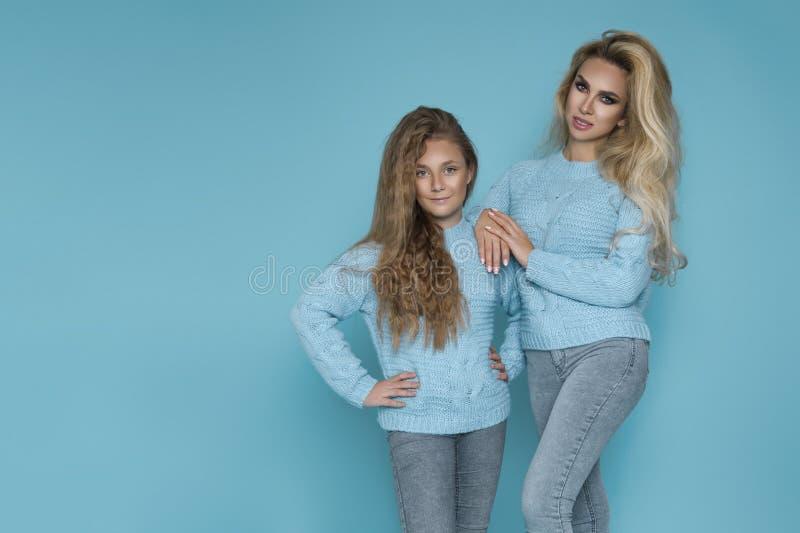 Meninas louras bonitas, mãe com a filha na roupa do inverno do outono em um fundo azul no estúdio fotos de stock royalty free