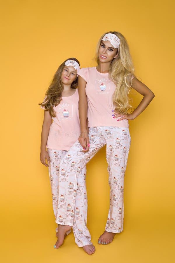 Meninas louras bonitas, mãe com a filha nos pijamas em um fundo amarelo no estúdio imagem de stock royalty free