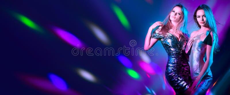 Meninas modelo quentes que dançam em luzes de néon UV Partido do disco Jovens mulheres 'sexy' com dança magro perfeita dos corpos imagem de stock