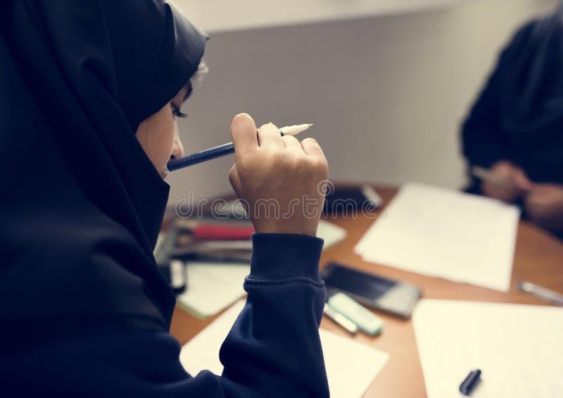 Meninas muçulmanas novas que fazem trabalhos de casa fotos de stock royalty free