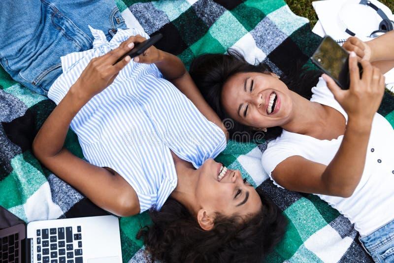 Meninas multi-étnicos dos amigos que usam telefones celulares fora no parque fotos de stock