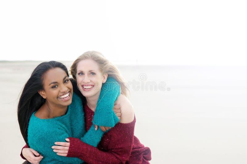 Meninas multiculturais que sorriem e que abraçam imagens de stock