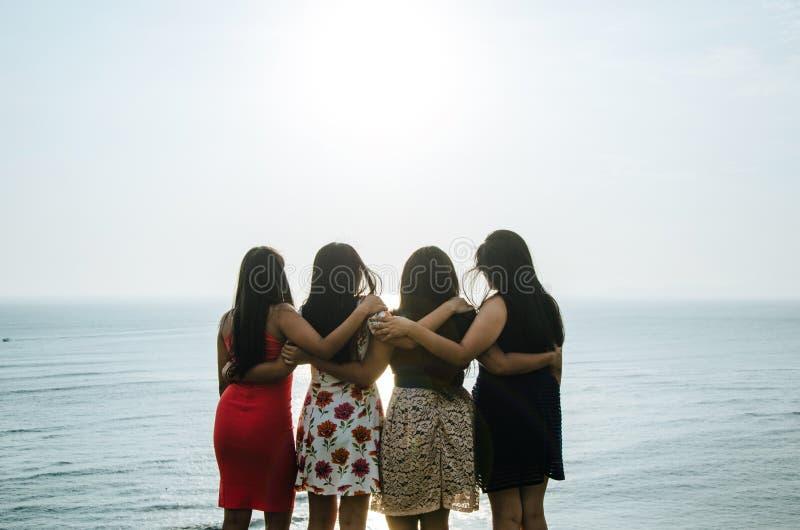 Meninas na frente do por do sol imagens de stock