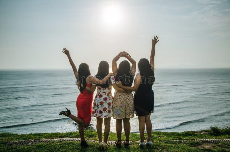Meninas na frente do por do sol fotos de stock