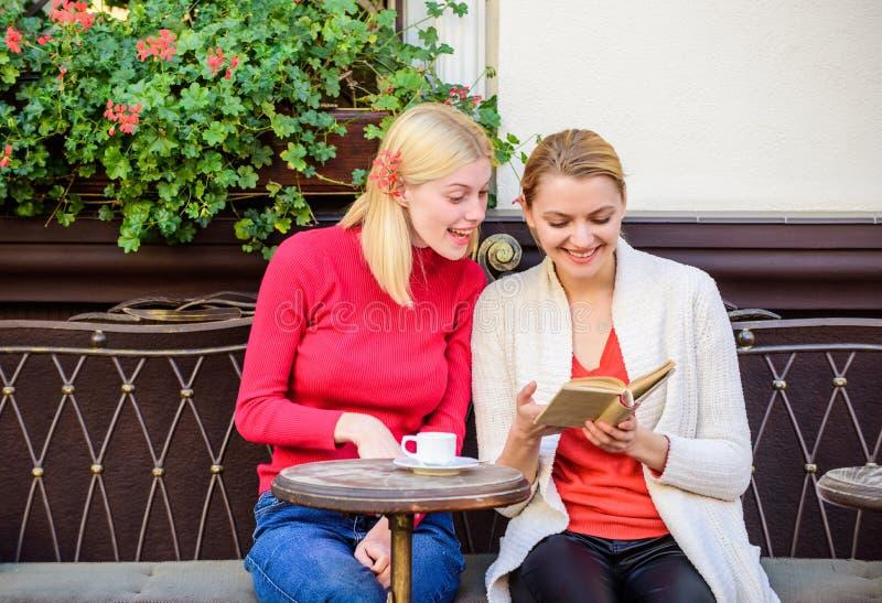 Meninas no livro de leitura do café Frienship f?mea Vida dos estudantes as meninas felizes preparam-se para o exame Sociedade mod fotografia de stock royalty free