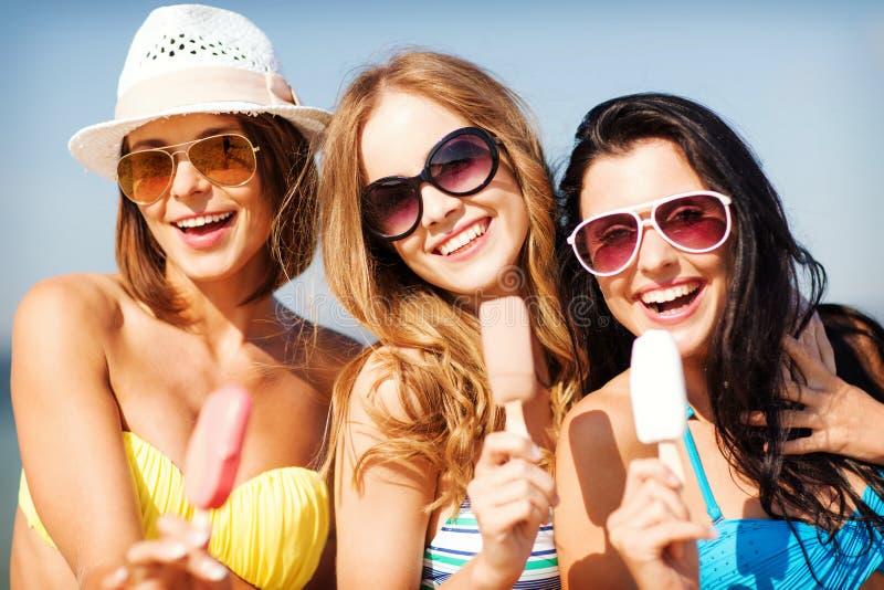 Meninas nos biquinis com gelado na praia imagens de stock