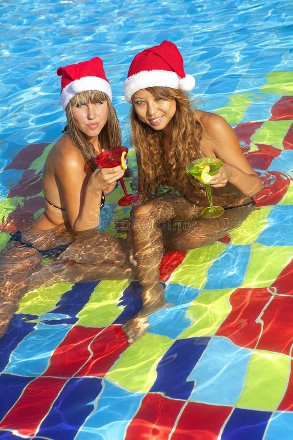 Meninas nos chapéus de Santa que sentam-se na piscina fotografia de stock