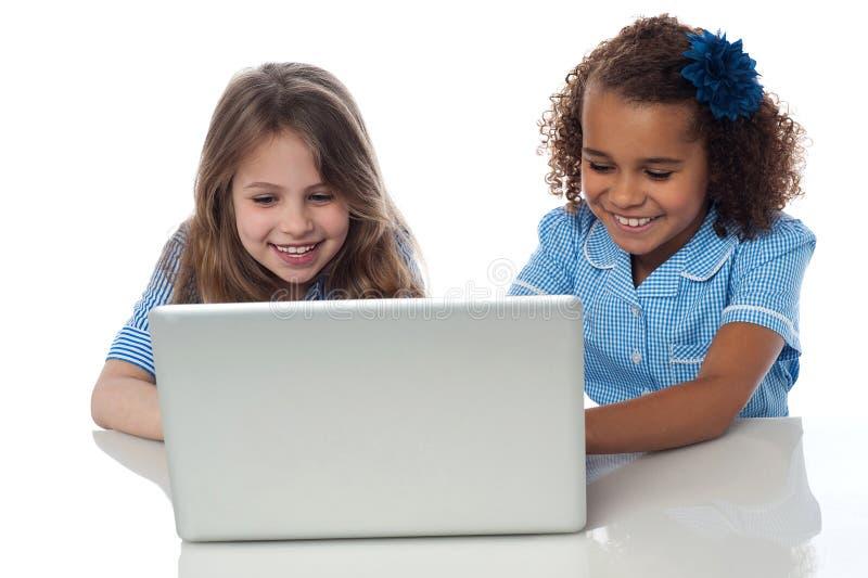 Meninas pequenas bonitos da escola com portátil fotos de stock royalty free