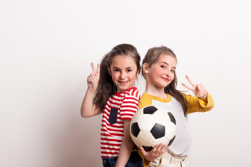 Meninas pequenas com uma bola de futebol que está em um estúdio, mostrando o sinal da vitória imagens de stock royalty free