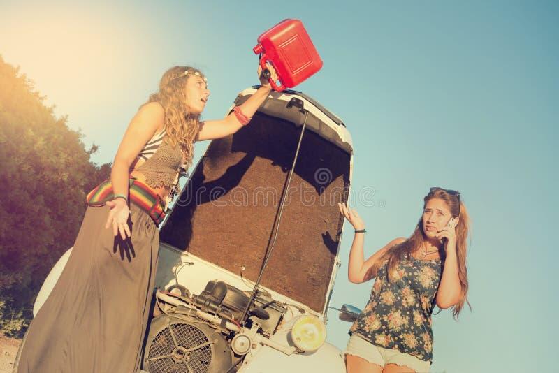 Meninas perto de um carro sem o combust?vel imagens de stock