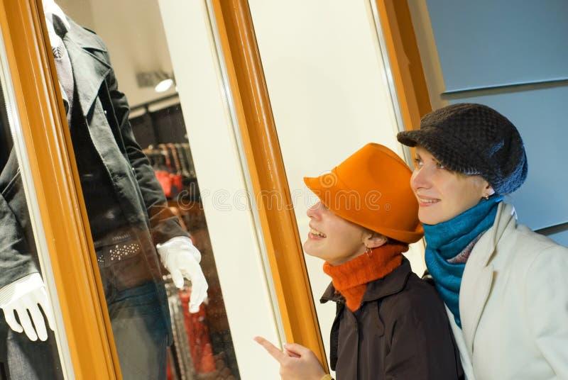 Meninas perto do indicador da loja foto de stock