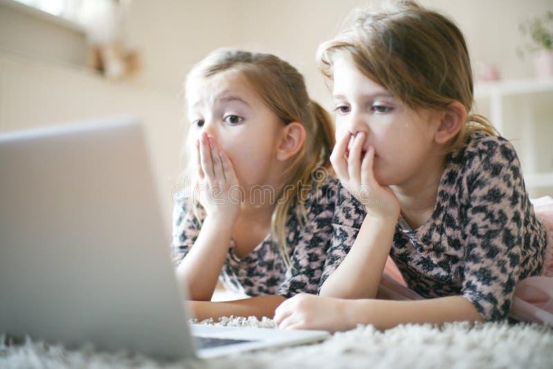 Meninas prées-escolar que usam o portátil em casa fotografia de stock