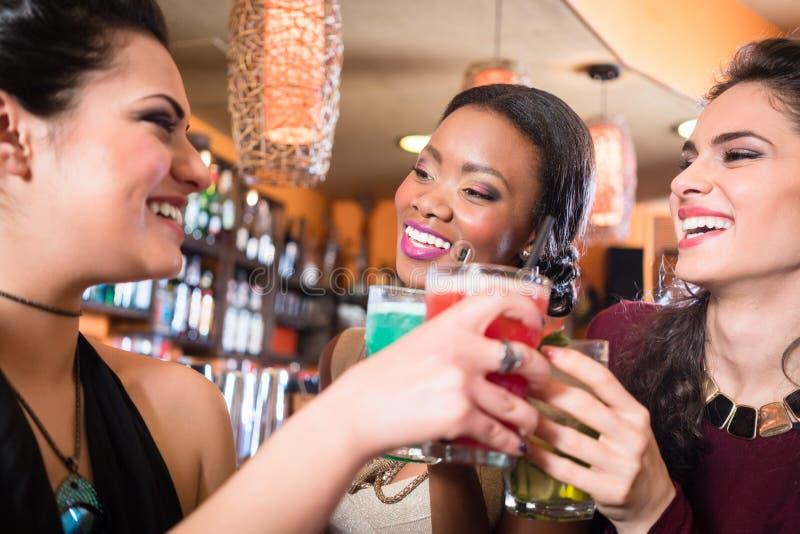 Meninas que apreciam a vida noturno em um clube, cocktail bebendo imagem de stock