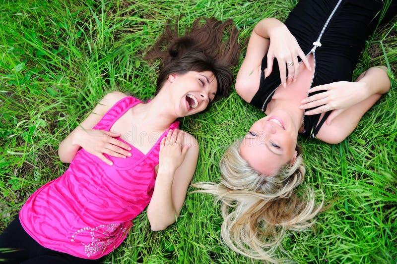 Meninas que colocam na grama imagem de stock royalty free