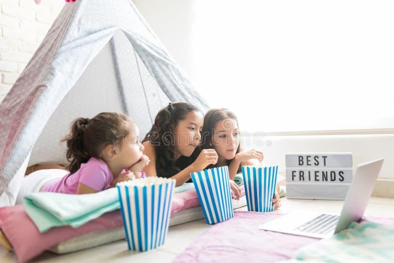 Meninas que comem pipocas ao olhar o filme no portátil na tenda imagens de stock