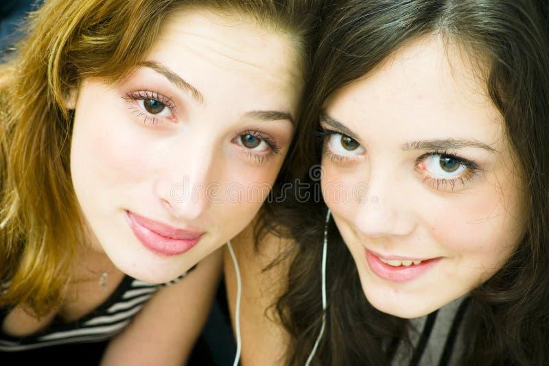 Meninas que compartilham de auscultadores imagens de stock