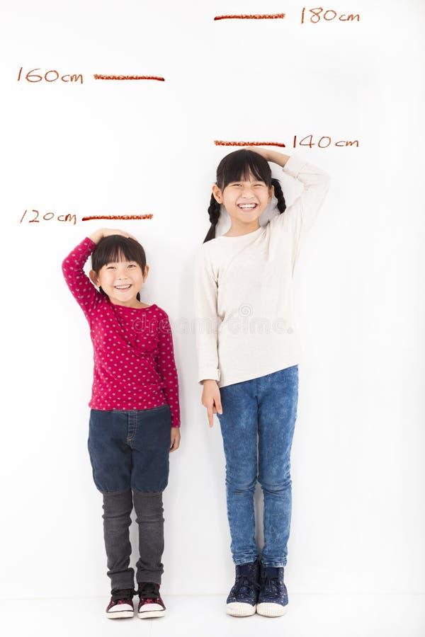 Meninas que crescem acima e contra a parede fotografia de stock