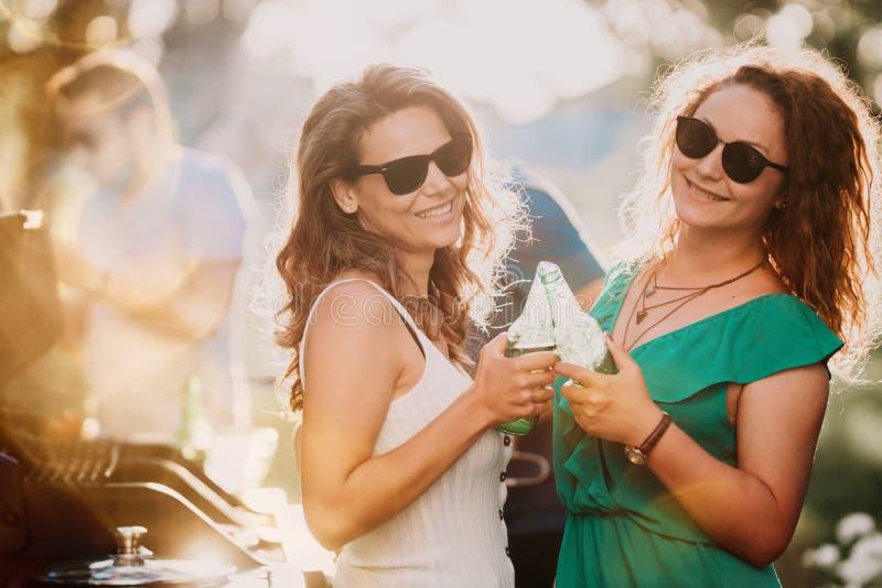 Meninas que dançam no partido do assado, amigos que comem cervejas e indivíduos que cozinham no fundo fotos de stock royalty free