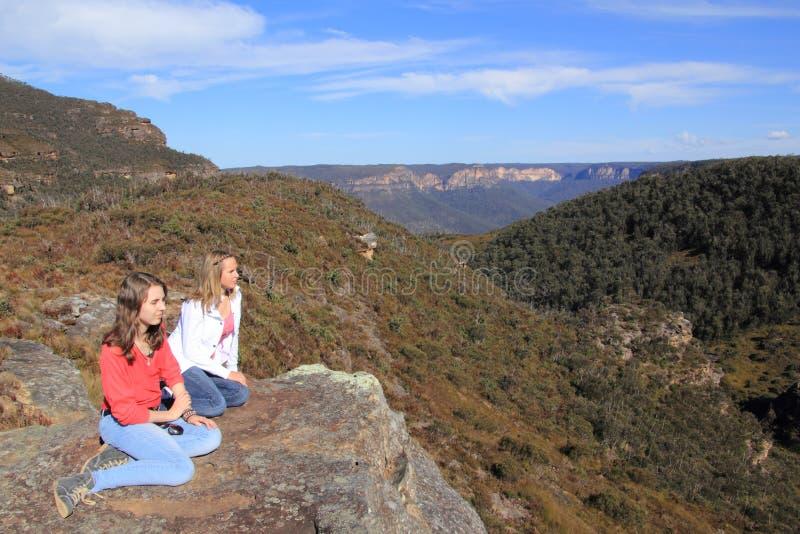Meninas que descansam em bancos do Mt foto de stock